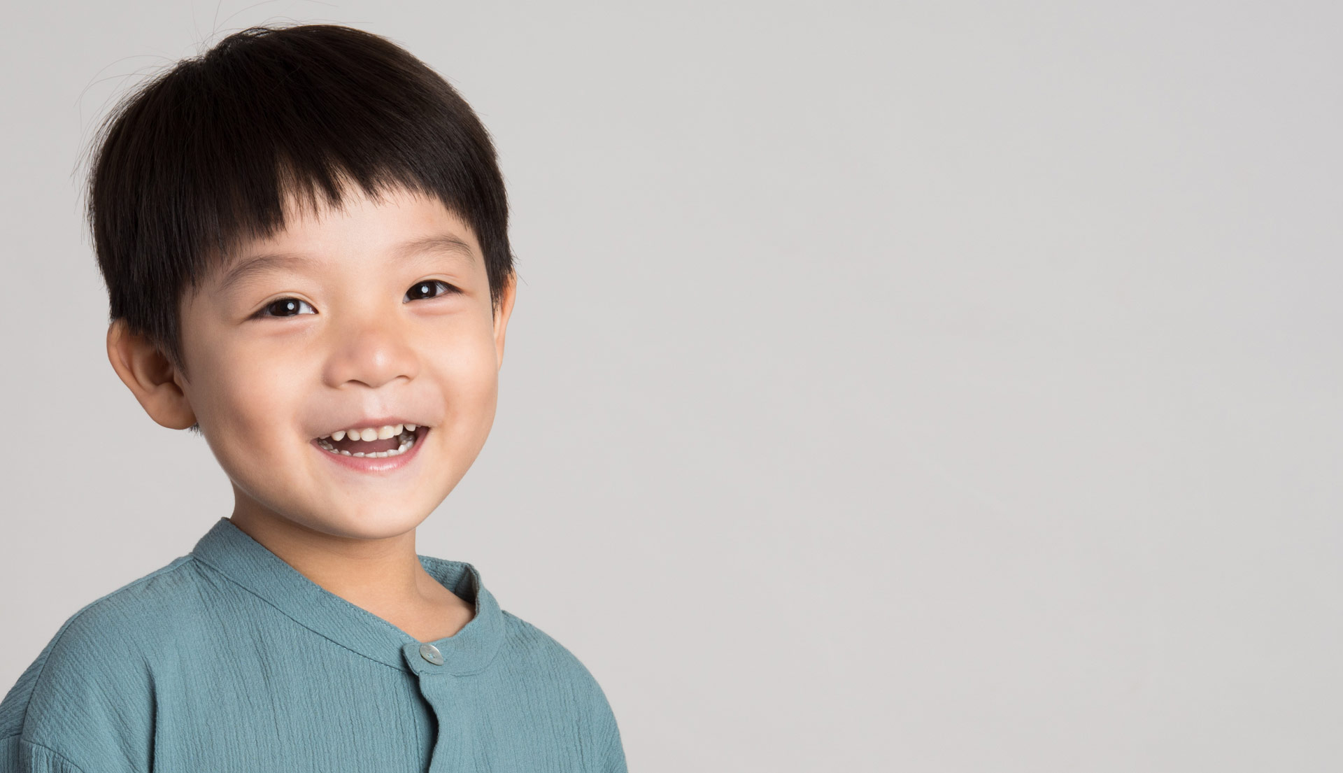 Young Asian American boy smiling with healthy teeth